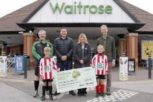Nova United members receiving a cheque from Waitrose in Newport