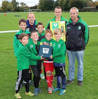 Nova United chairman, Ted Bowen (right), with players, coaches and the new defibrillator and it's mounting case.